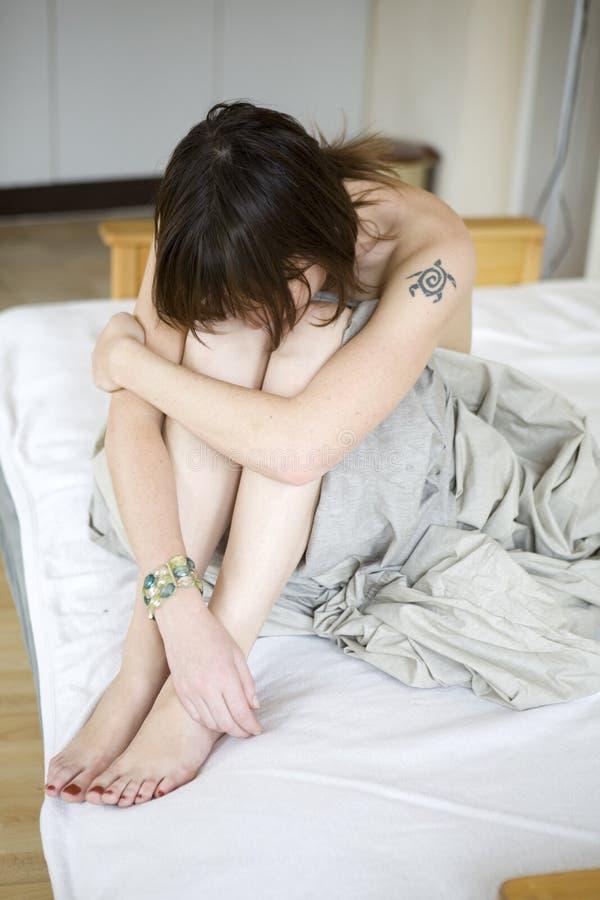 Ernstige droevige vrouwenzitting op bed stock afbeelding