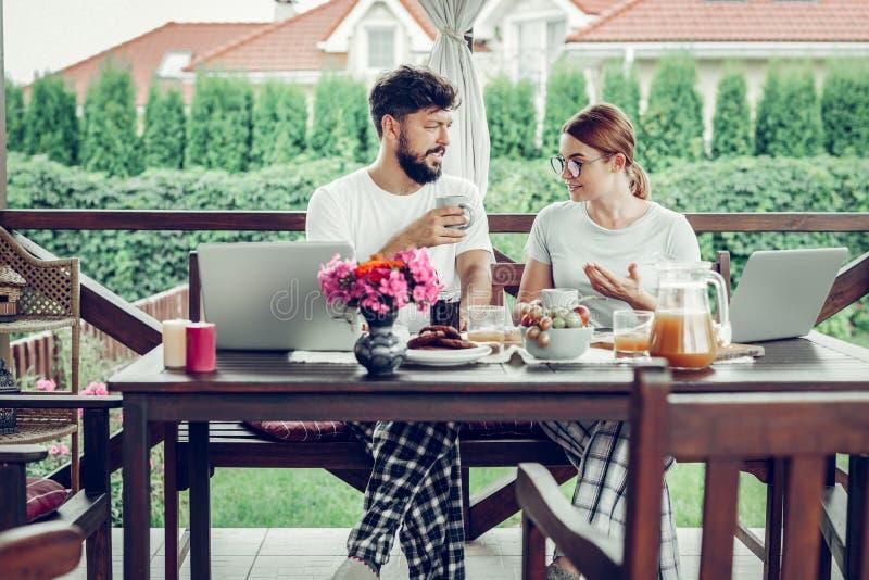Ernstige echtgenoten die het werk bespreken tijdens ontbijt in de tuin stock afbeelding