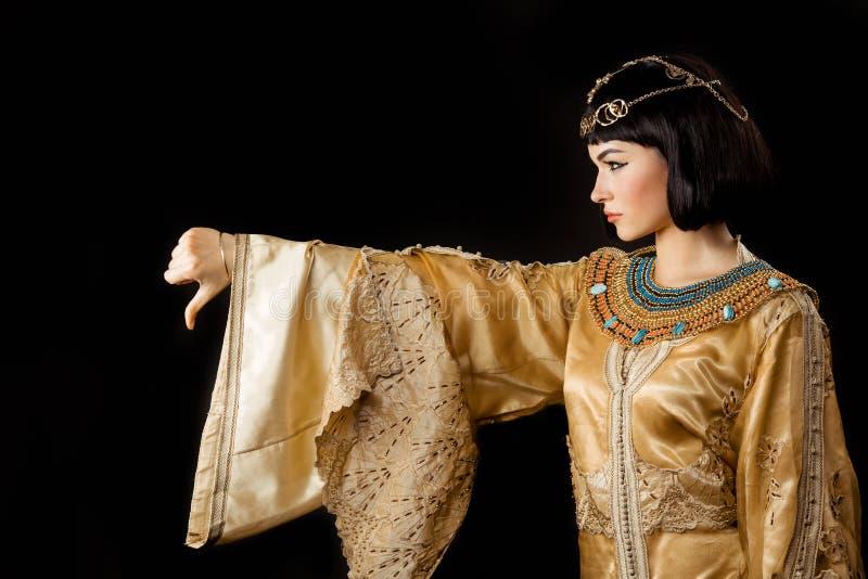 Ernstige Egyptische vrouw zoals Cleopatra met duimen onderaan gebaar, op zwarte achtergrond royalty-vrije stock foto