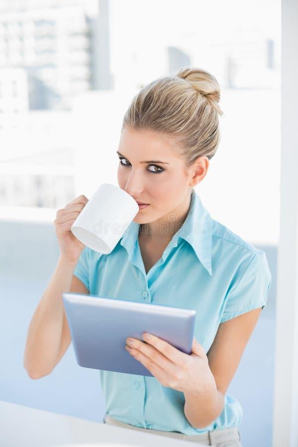 Ernstige elegante vrouw die tablet gebruiken terwijl het drinken van koffie stock afbeeldingen