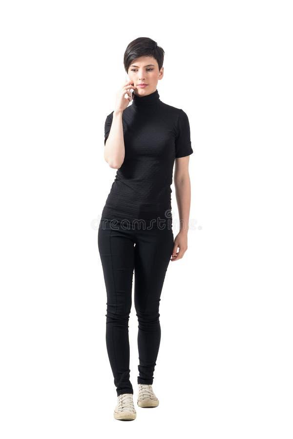 Ernstige elegante vrouw in zwarte col die en op de mobiele telefoon lopen spreken royalty-vrije stock foto's