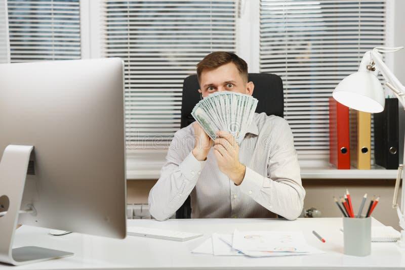 Ernstige en in beslag genomen bedrijfsmens in overhemdszitting bij het bureau, die bij computer met moderne monitor werken Manage royalty-vrije stock fotografie