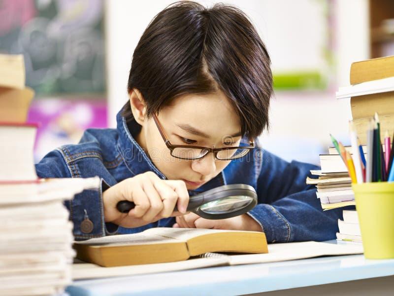 Ernstige en nieuwsgierige Aziatische elementaire schooljongen stock foto