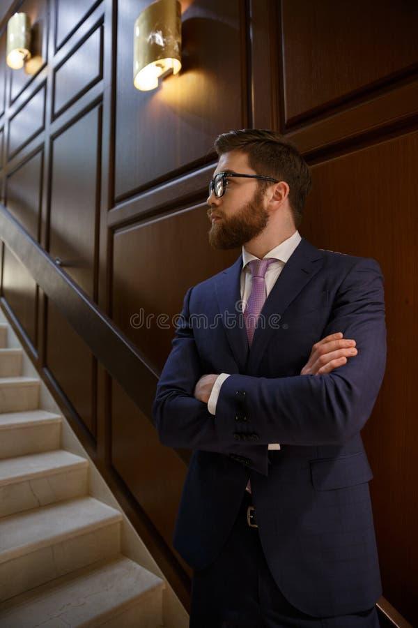 Ernstige gebaarde jonge zakenman die zich met gekruiste wapens bevinden royalty-vrije stock foto's