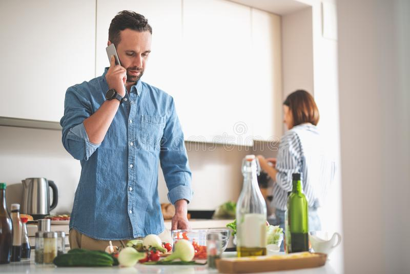 Ernstige gebaarde mens die op cellphone in keuken spreken royalty-vrije stock afbeeldingen