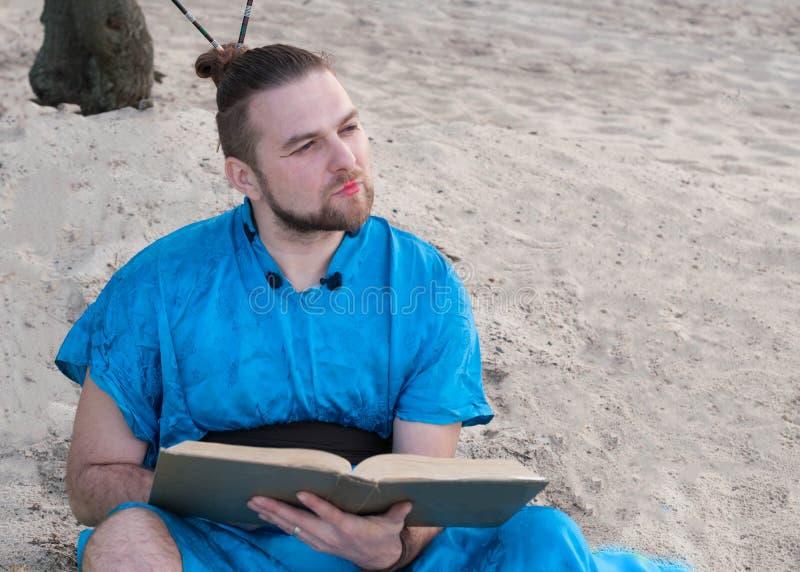 ernstige gebaarde mens met broodje op hoofd in blauwe kimonozitting, holdings groot boek royalty-vrije stock fotografie