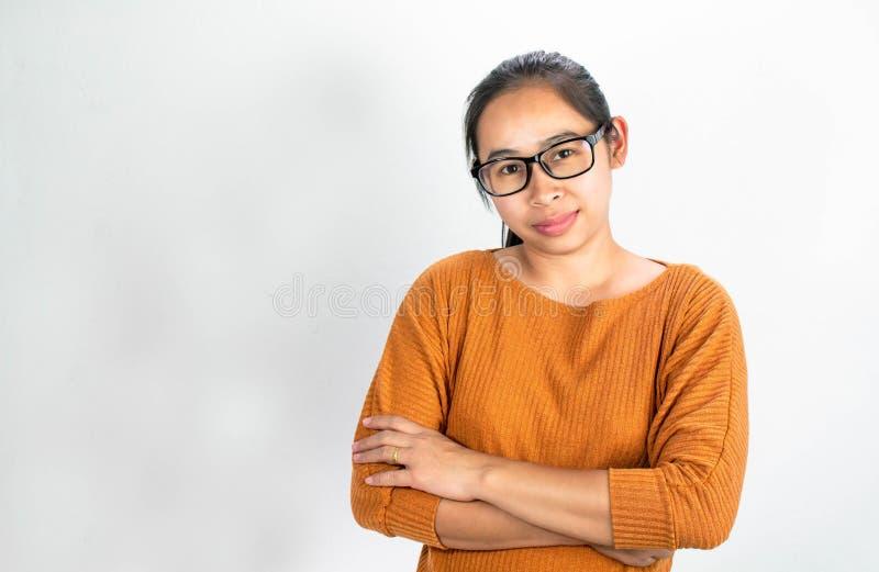 Ernstige gezichts Aziatische vrouw die voor oranje overhemd en oogglazen oppassen; De status van en de kruising van zijn wapen op royalty-vrije stock afbeeldingen