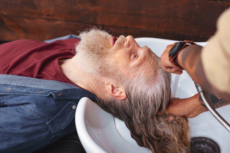 Ernstige grijs-haired mannelijke persoon het bezoeken salon stock foto