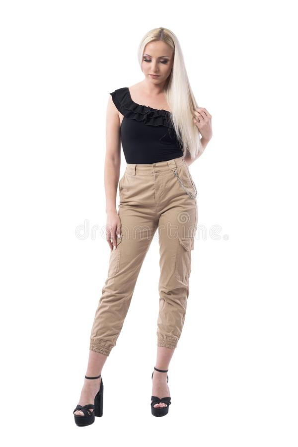 Ernstige hartelijke blondeschoonheid wat betreft rechtstreeks lang haar die neer eruit zien stock foto