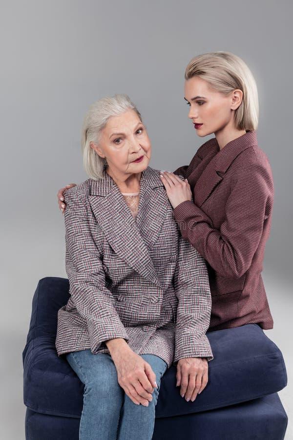 Ernstige hogere grijs-haired vrouwenzitting op fluweelbank met haar dochter stock afbeelding