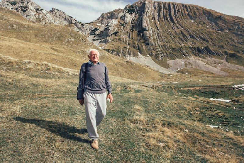 Ernstige hogere mens op de bergenweg royalty-vrije stock foto's