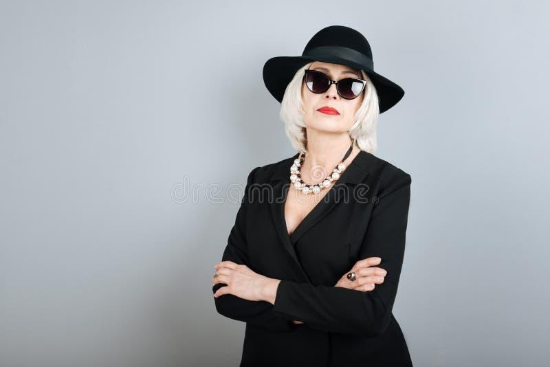 Ernstige hogere vrouw die haar wapens over borst kruisen royalty-vrije stock afbeeldingen