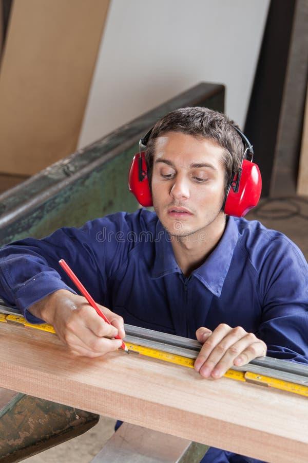 Ernstige homosexueel die een plank in zijn workshop meten stock afbeeldingen