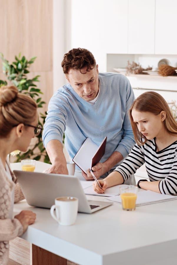 Ernstige houdende van ouders die hun dochter met thuiswerk helpen royalty-vrije stock afbeeldingen