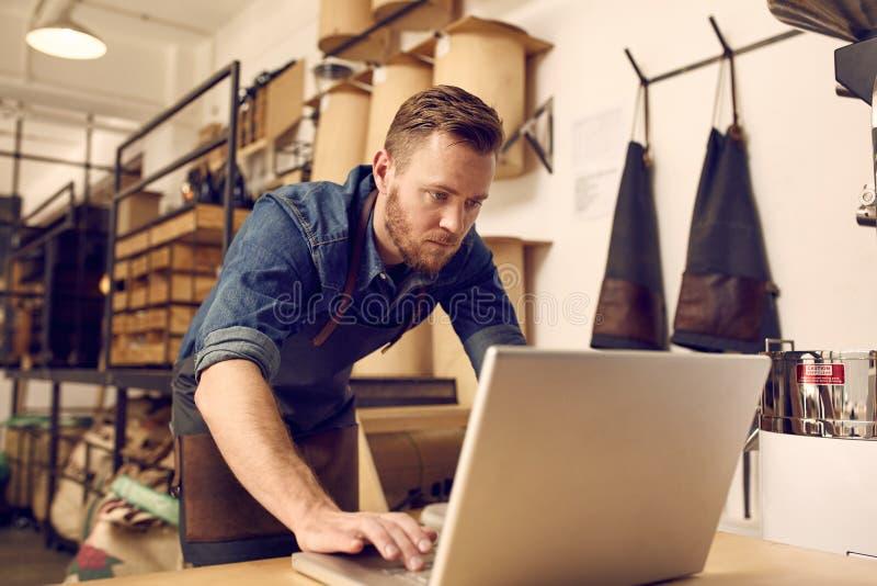 Ernstige jonge bedrijfseigenaar die laptop in zijn workshop met behulp van stock afbeeldingen