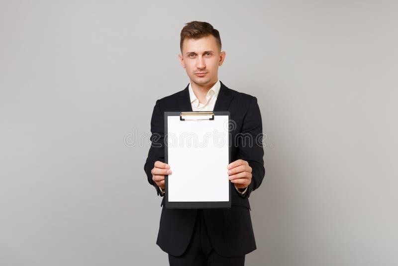 Ernstige jonge bedrijfsmens in klassiek zwart kostuum, het klembord van de overhemdsholding met lege lege geïsoleerde bladwerkrui stock afbeelding