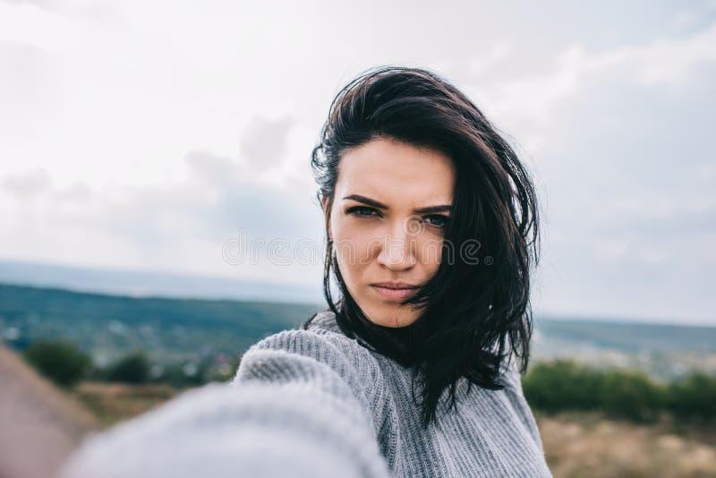Ernstige jonge donkerbruine vrouw die zelfportret nemen en tegen weide en donkere hemelachtergrond stellen Het leuke wijfje neemt stock foto