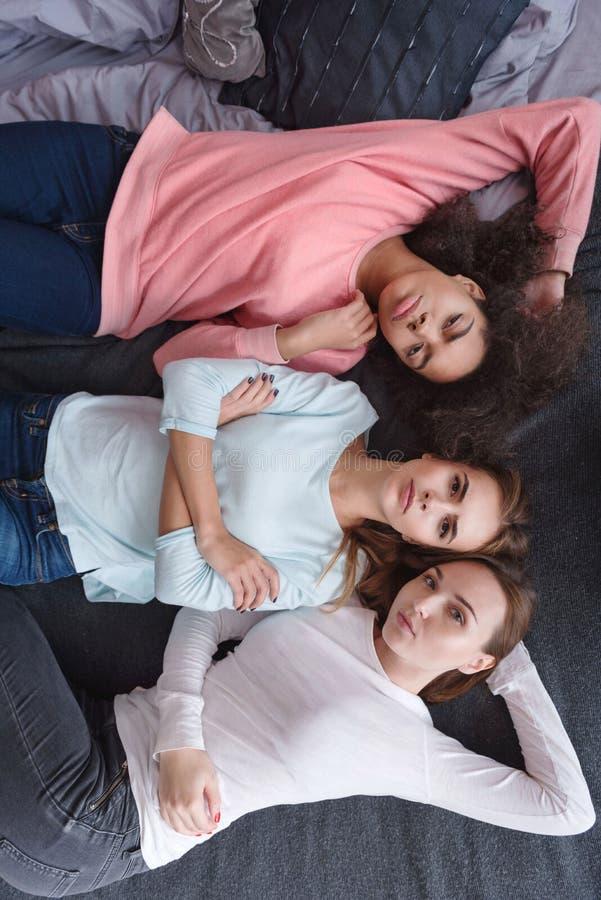 Ernstige jonge meisjes die op het bed in de slaapkamer liggen stock foto's