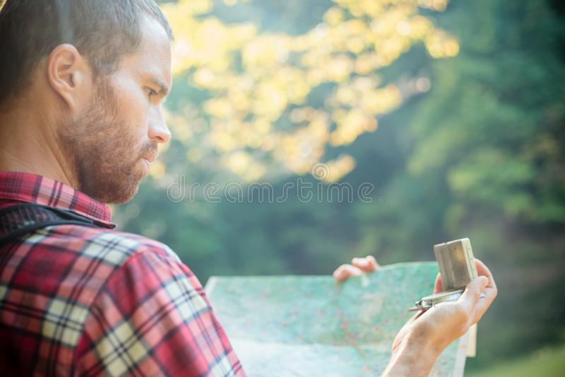 Ernstige jonge mens die gebruikend kompas en een kaart navigeren Wandeling door bos stock afbeelding
