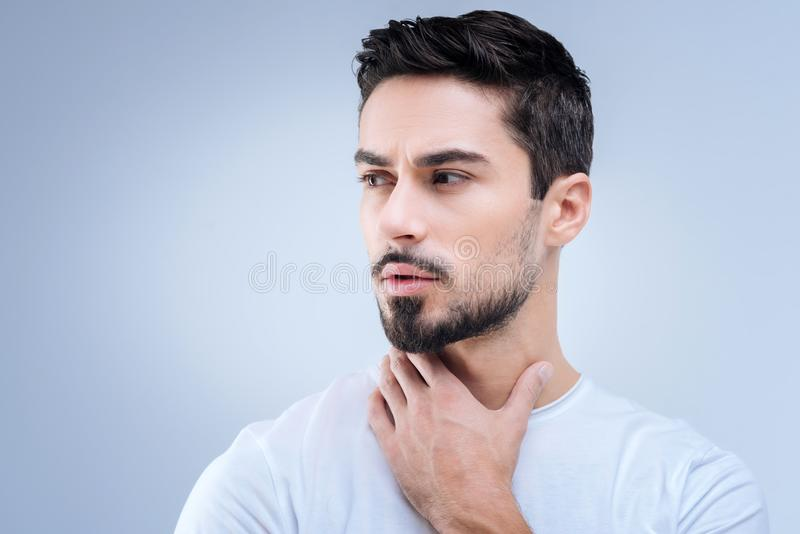 Ernstige jonge mens die ongerust gemaakt terwijl wat betreft zijn hals kijken stock fotografie