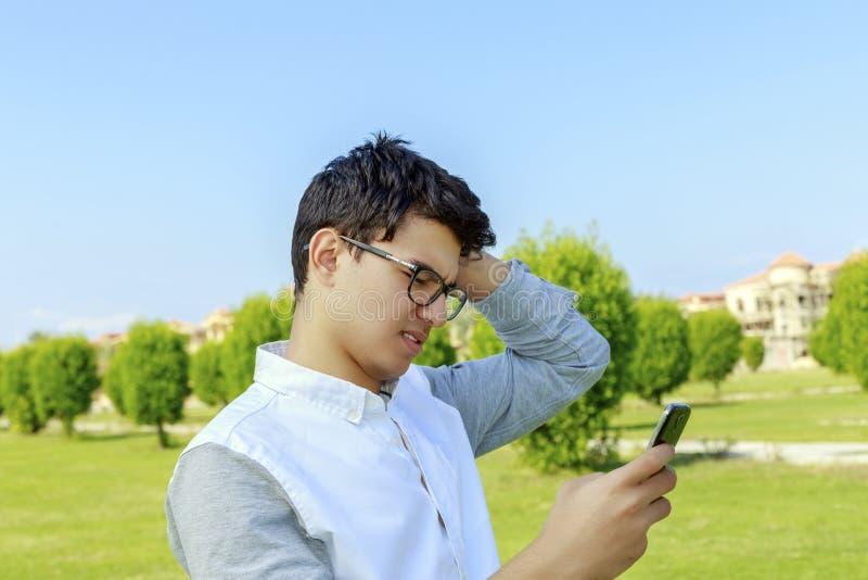 Ernstige jonge mens openlucht met mobiele telefoon stock afbeelding