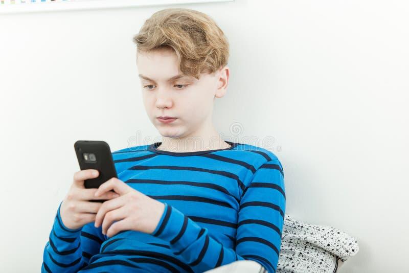 Ernstige jonge tiener die een bericht lezen stock fotografie