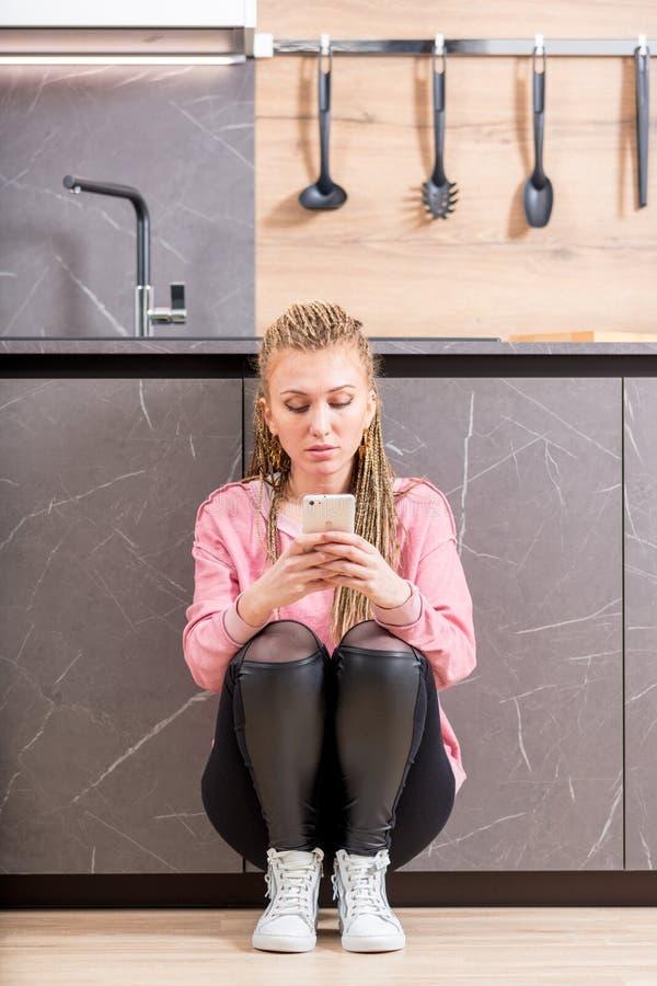 Ernstige in jonge vrouw die mobiel haar gebruiken royalty-vrije stock afbeeldingen