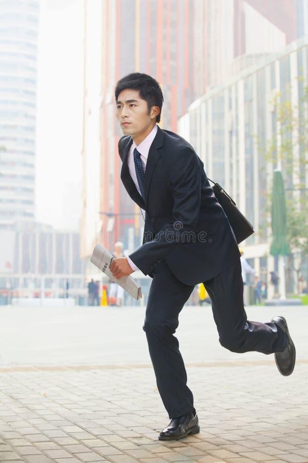 Ernstige, jonge zakenman in een kostuum die in het bedrijfsdistrict in Peking, China lopen royalty-vrije stock foto