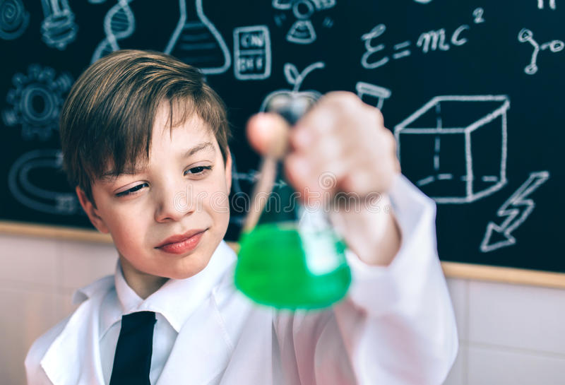 Ernstige jongen die fles met chemische vloeistof kijkt stock foto