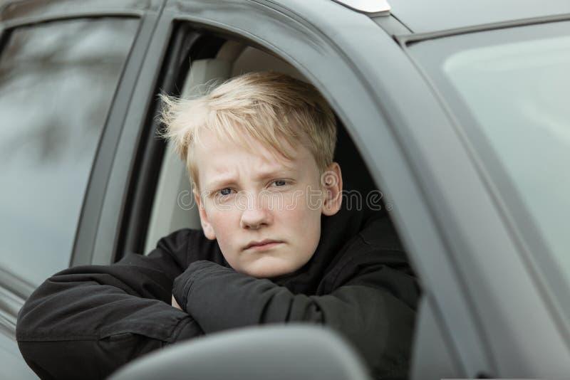 Ernstige jongen met gevouwen wapens in auto royalty-vrije stock afbeelding