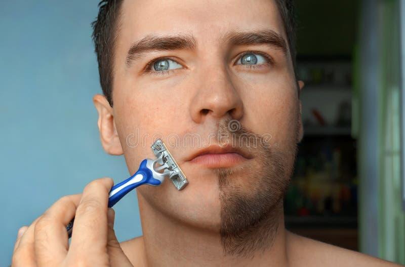 Ernstige kerel die zijn baard scheren stock afbeelding