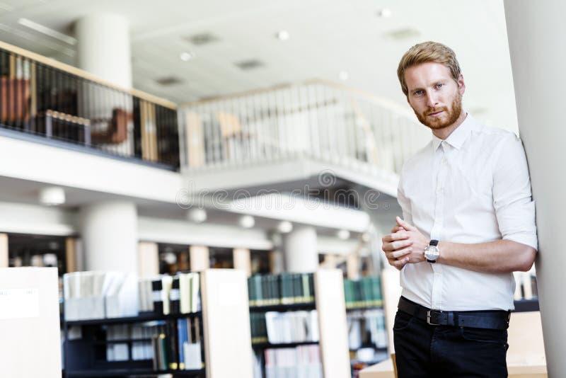Ernstige knappe student in bibliotheek royalty-vrije stock afbeelding