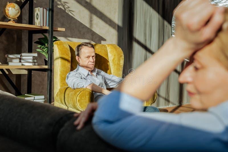 Ernstige kortharige oude mens die droevig op zijn ongelukkige vrouw kijkt stock foto