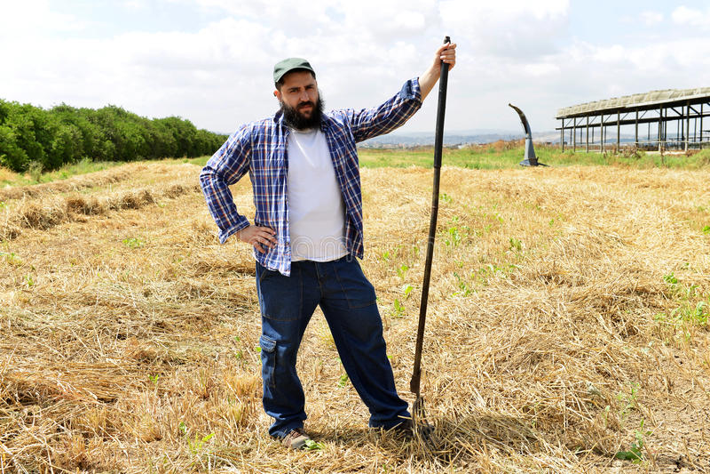 Ernstige landbouwer die op zijn vork na het harde werkdag leunen royalty-vrije stock foto