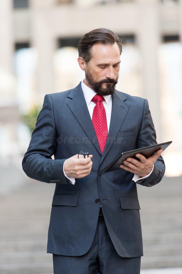 Ernstige leraar die de nota's in zijn tablet en het denken bekijken royalty-vrije stock afbeelding