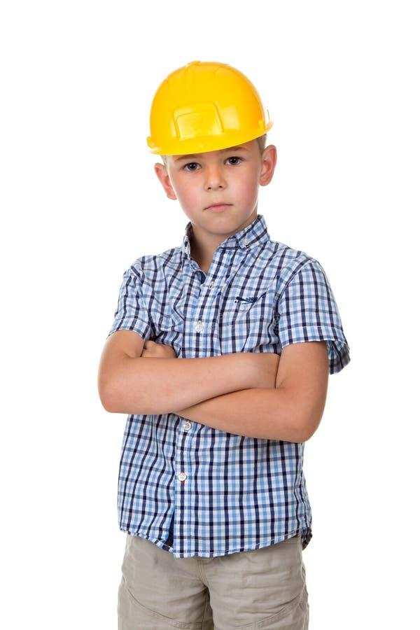 Ernstige leuke jongen in blauw geruit overhemd, grijze jeans en gele die de bouwhelm, op witte achtergrond wordt geïsoleerd stock afbeeldingen