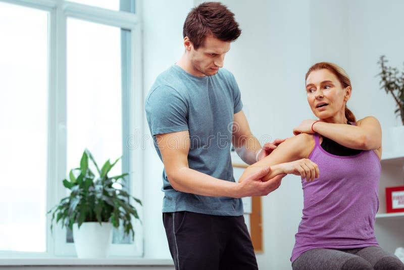 Ernstige mannelijke masseur die zijn pati?ntenschouder bekijken stock afbeeldingen