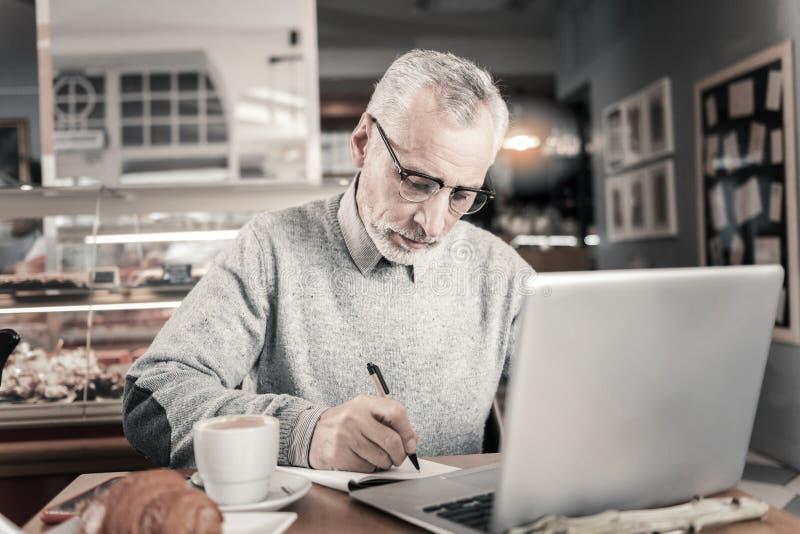 Ernstige mannelijke persoon het schrijven ideeën op papier stock fotografie