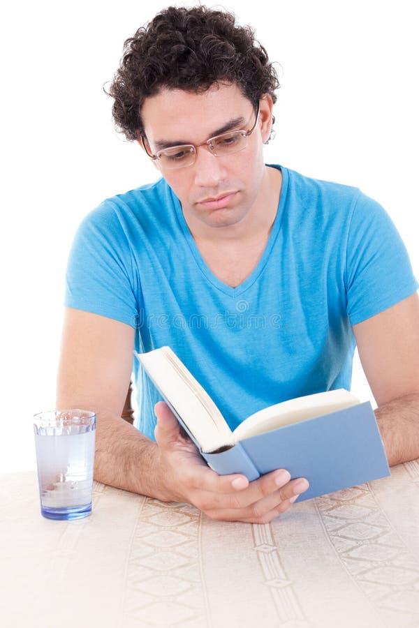Ernstige mens in blauwe t-shirtzitting bij lijst en lezingsboek royalty-vrije stock afbeelding