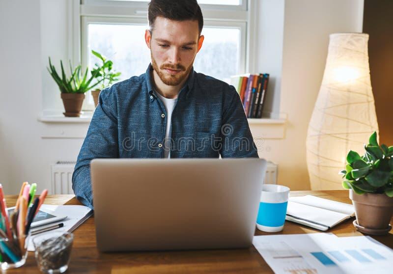 Ernstige mens die aan laptop werken stock fotografie