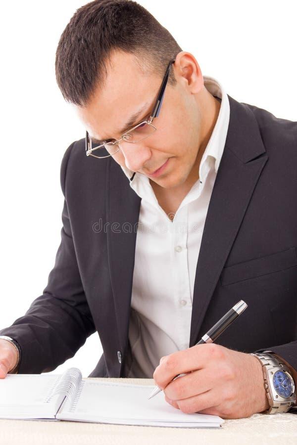 Ernstige mens die in kostuum met glazen in notitieboekje schrijven royalty-vrije stock foto's