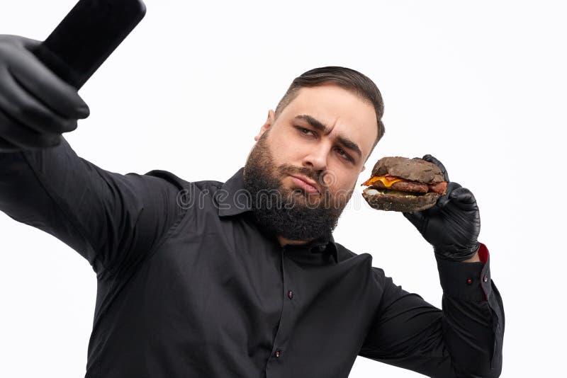 Ernstige mens die selfie met hamburger nemen royalty-vrije stock fotografie