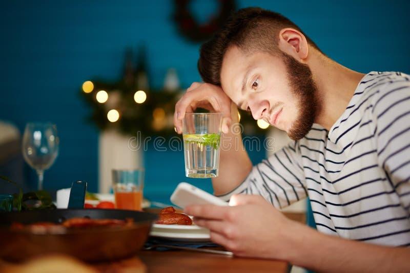 Ernstige mens die smartphone gebruiken bij dinerpartij stock fotografie