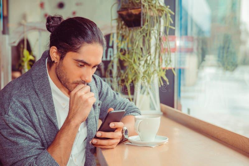 Ernstige mens die die telefoon bekijken, door nieuws ongerust wordt gemaakt dat hij heeft ontvangen stock fotografie
