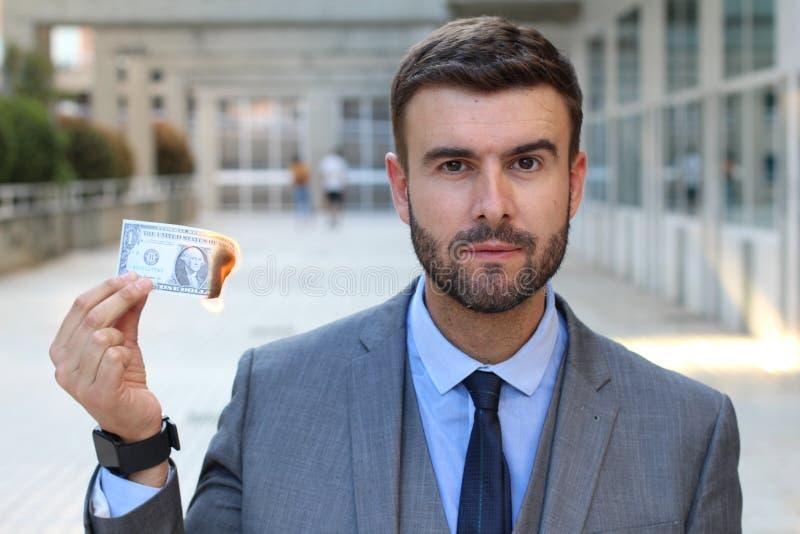 Ernstige mens met dollarrekening op brand royalty-vrije stock foto