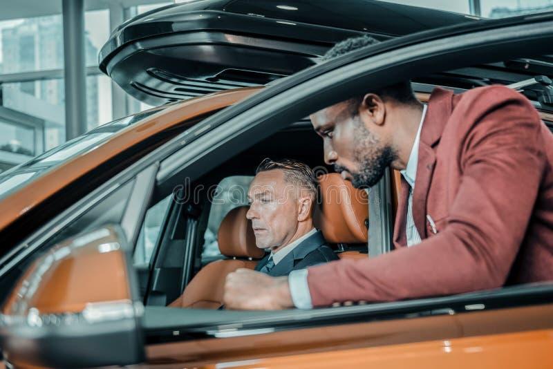 Ernstige mensenzitting in een auto in salon royalty-vrije stock foto's