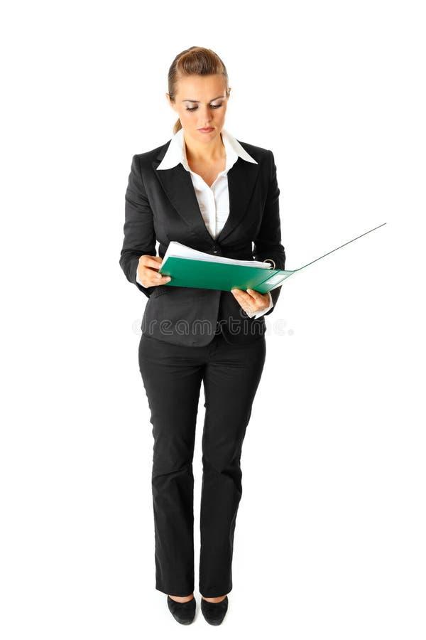 Ernstige moderne bedrijfsvrouw die documenten onderzoekt stock afbeelding