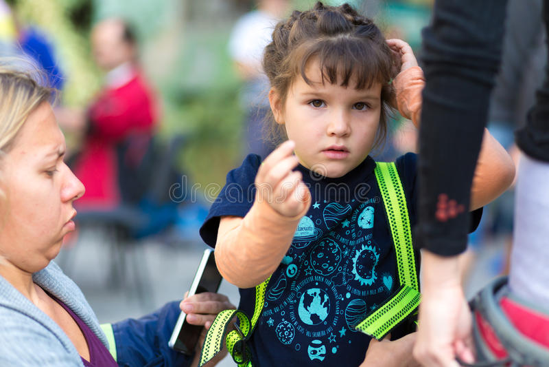 Ernstige Moeder die weinig Kind voor klim voorbereiden stock fotografie