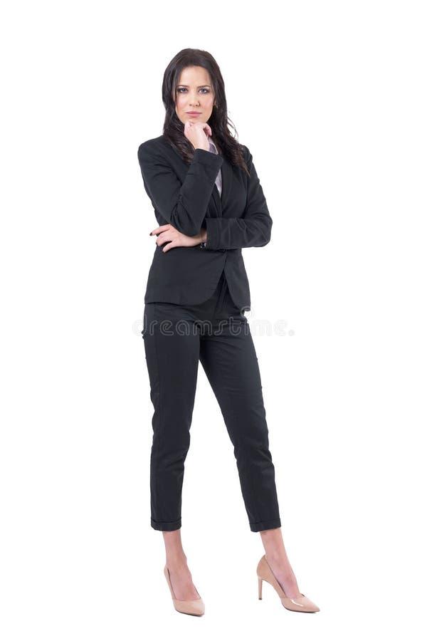 Ernstige mooie bedrijfsdame die in zwart kostuum met hand op kin camera bekijken stock fotografie