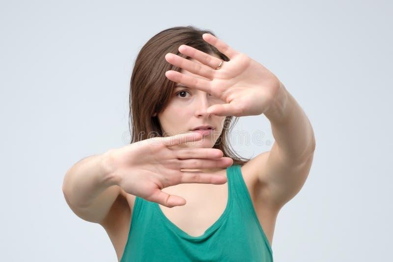 Ernstige mooie vrouw die einde maken het gebaar van de tekenpalm overhandigen stock foto's